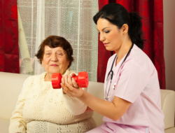 nurse assisting an old woman to exercise